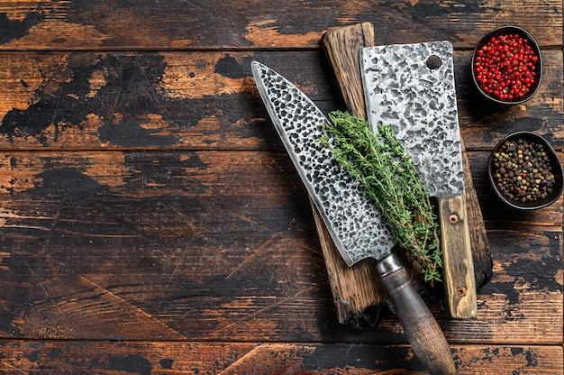 古い肉屋の肉切り包丁とナイフ。暗い木の背景。