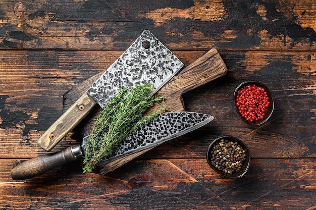 古い肉屋の肉切り包丁とナイフ。暗い木製の背景
