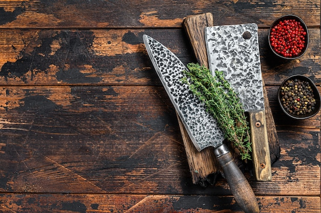Old butcher meat cleaver and knife. dark wooden background.