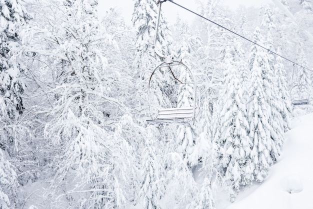 Old cable lift with no passengers going across coniferous forest mountain ski resort near the town of kolasin, montenegro after a heavy snowfall