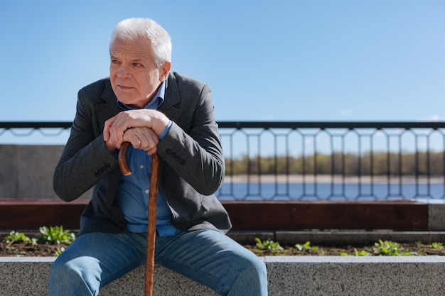 Old cagey sorrowful man sitting on concrete stab crossing his hands while looking at young people