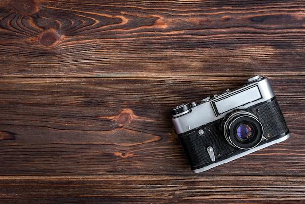 Старый фотоаппарат и фотобумага пустой на деревянном