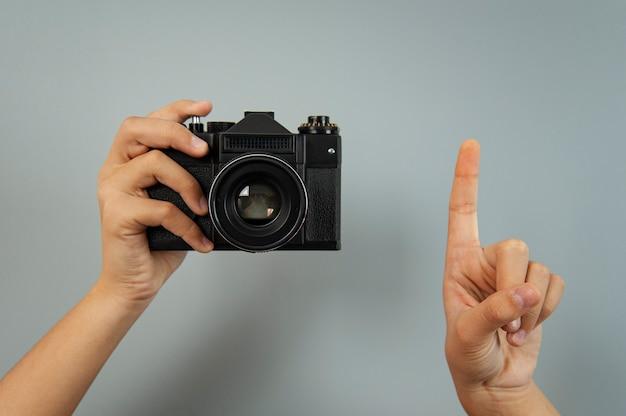 灰色の背景に女性の手で古いカメラ