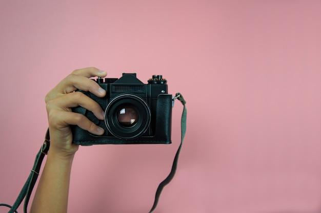 ピンクの背景に片方の女性の手で古いカメラ
