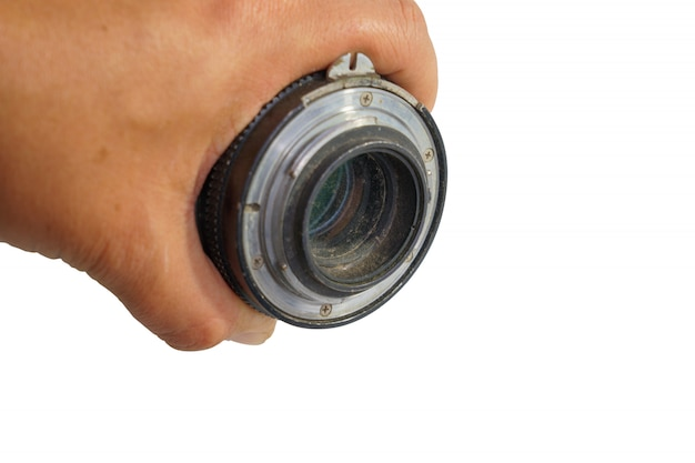 Old camera lens in hand