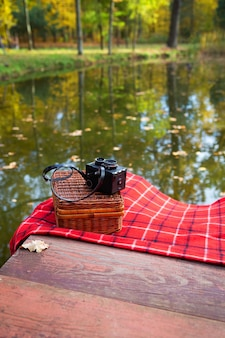 Old camera lies on a suitcase on a red plaid blanket. wooden bridge near the lake.
