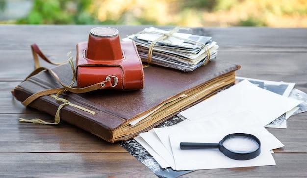 Старый фотоаппарат с фотографиями и фотоальбом на деревянном столе