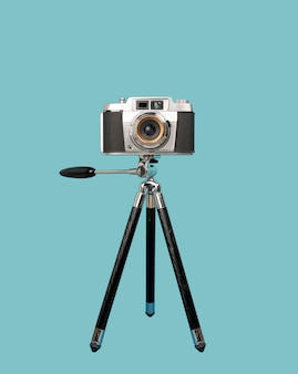Old camera on tripod isolated on blue background
