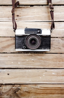 Old camera and on wooden table, space for text or image for design work