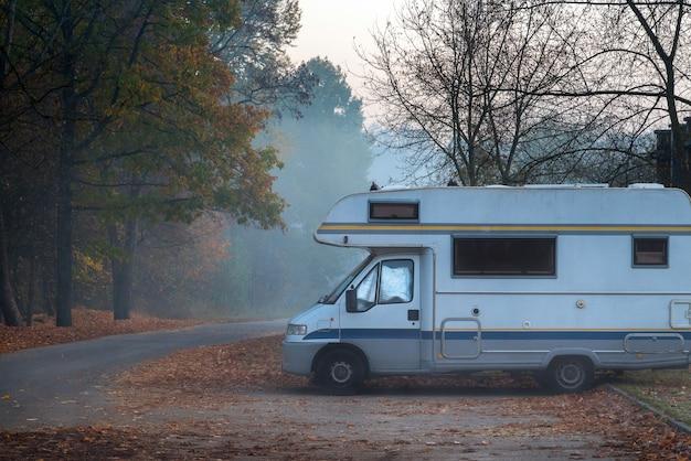 오래 된 캠퍼 밴은 안개가 자욱하고 추운 가을 아침에 도로 옆에 주차되었습니다.