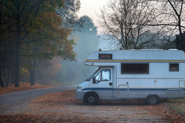 Old camper van parked in next to the road on foggy and cold autumn morning.