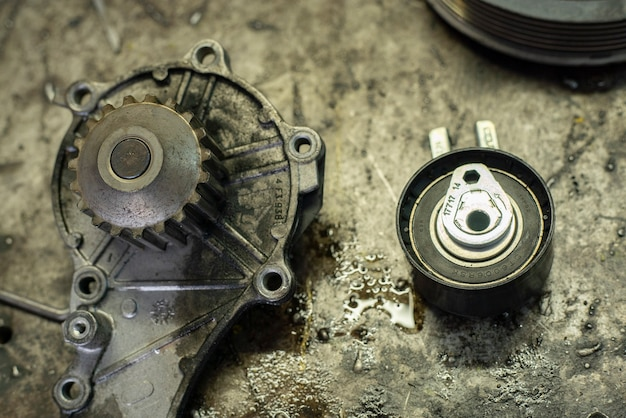 작업장 벤치에 있는 오래된 자동차 엔진 부품