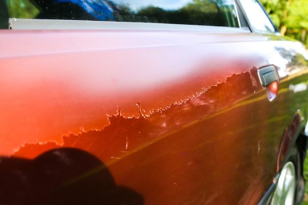 ボンネットに傷のある古い車。車両の塗装を剥がしました。