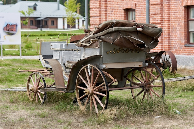 Старый экипаж в сельском дворе в летний день