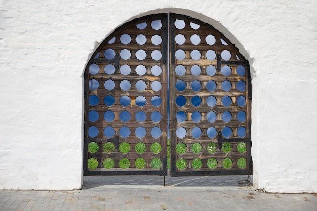 Old carved door in the white wall