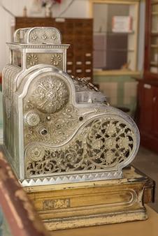Старый кассовый аппарат стоит на прилавке в магазине
