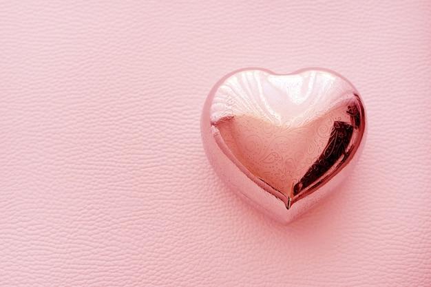 ピンクの革の背景にハートの形をした古い棺。パターン、孤立したハートの形をしたシルバーボックス。バレンタイン・デー。