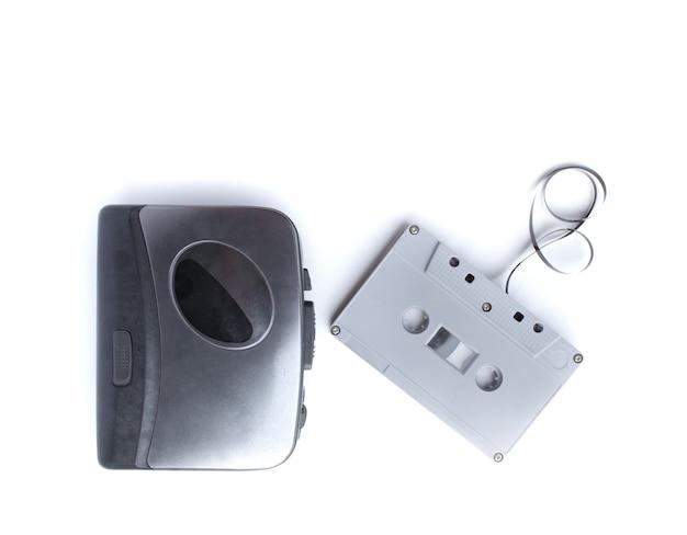 Старый кассетный плеер и кассета, изолированные на белом пространстве
