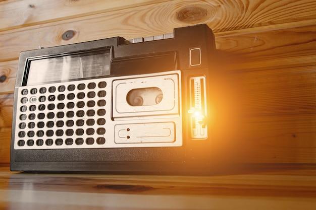 木製の背景に古いカセットテープレコーダー。