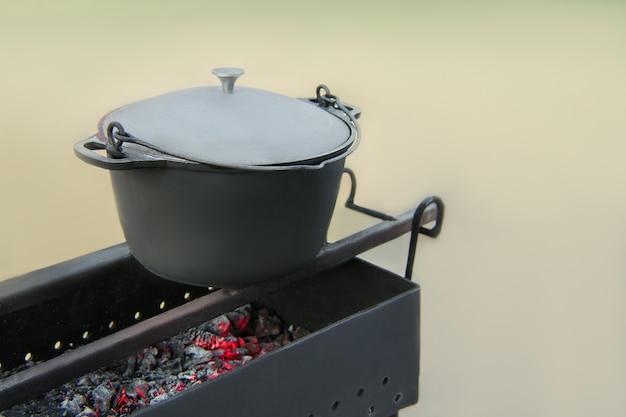 불타는 뜨거운 불길과 그릴에 그을음에 오래 된 주철 가마솥 팬. 자연 속에서 요리하기