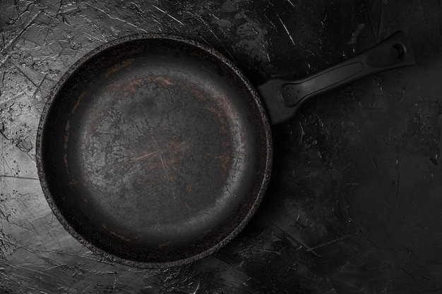 Old cast-iron empty frying pan, top view