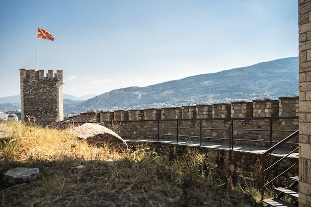 Old castle with the flag of macedonia on it surrounded by hills covered in greenery