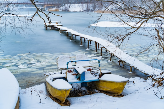 Old catamaran in the winter on the snow coast of the frozen river next to the long bridge.