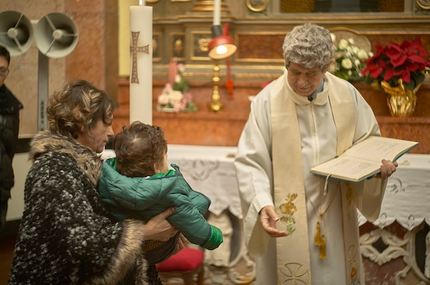 Old catholic priest celebrates baptism in an italian church