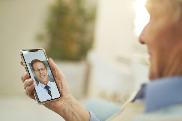 스마트폰을 보고 의사와 온라인 채팅을 하는 백인 노인