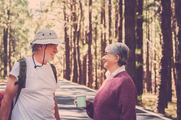 古い白人の成熟したカップルは、山の高い松林でのトレッカーの野生の休暇の旅の間に笑顔で楽しんでいます-代替の野生の人々は永遠に一緒に旅行します