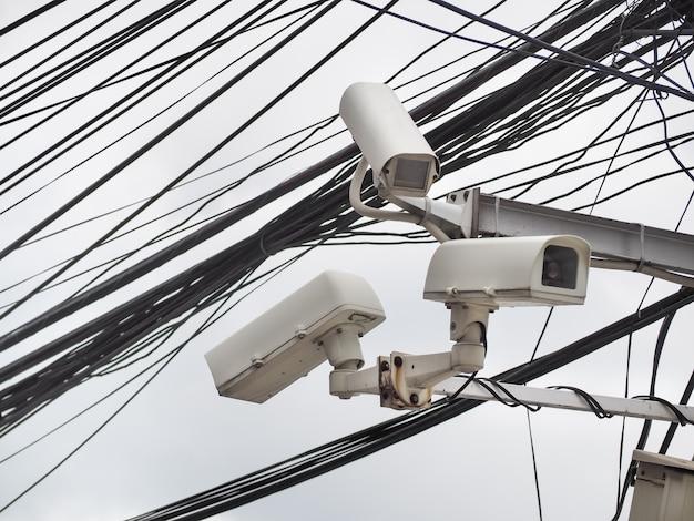Старая безопасность камеры видеонаблюдения, висящая на хаосе кабелей и проводов, бангкок, таиланд Premium Фотографии