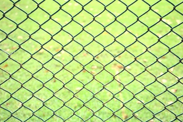 緑の芝生のフィールドの背景と前景に焦点を当てた古いチェーンリンクパターン抽象的なフェンス