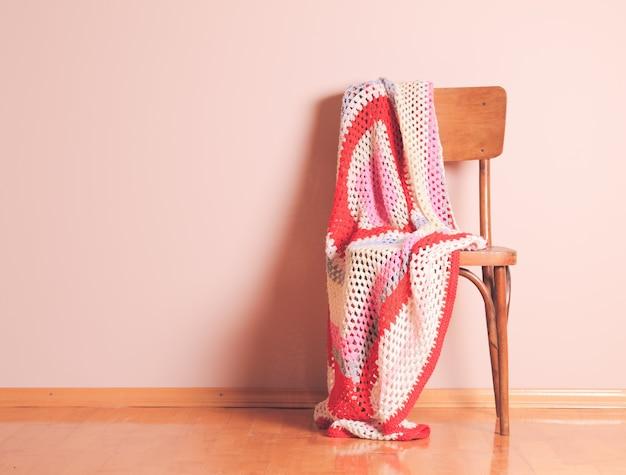 不注意に捨てられた毛布が付いている古い椅子
