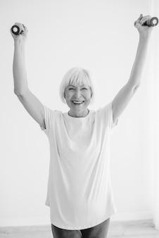 ダンベルでスポーツをしている古い陽気な女性アンチエイジスポーツ健康的なライフスタイルの概念