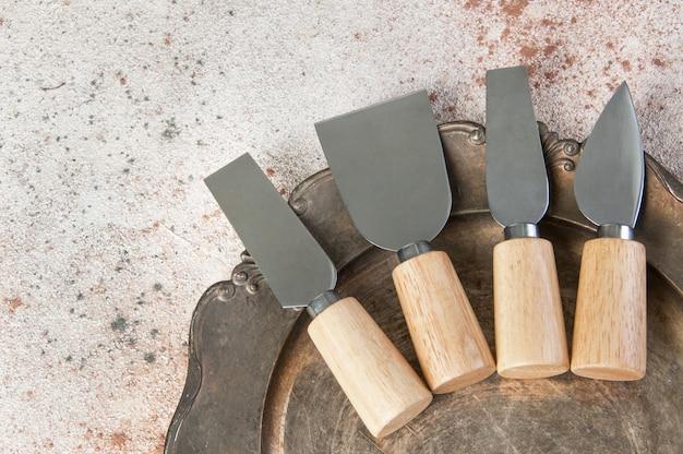 Старые сырные ножи на старинном металлическом блюде