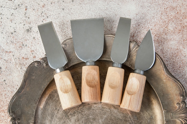 Old cheese knives on vintage metal dish