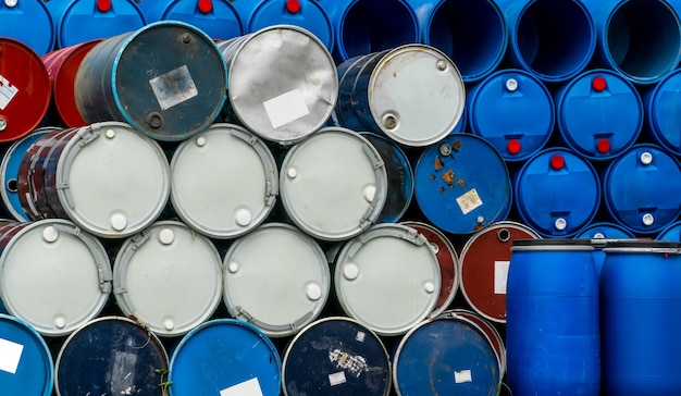 古い化学バレル。青と赤のドラム缶。スチールとプラスチックのオイルタンク。有毒廃棄物倉庫。