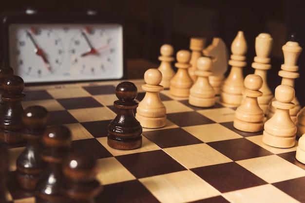 Старые шахматные часы на шахматной доске с фигурами, флаг в положении, указывающем на нехватку времени на темном фоне