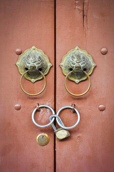 Старый китайский лев дверная ручка и замок на фоне коричневой деревянной двери