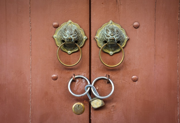 Old chinese lion doorknob and padlock on close brown wood door background