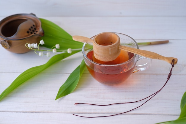 Old chinese tea shen puer in the form of a nest, brewed tea in a glass cup and a flower of silver lily of the valley on a white wooden table