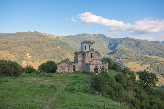山の古い教会、国立公園ドンバイ、コーカサス、ロシア。夏の風景、太陽の光の天気、劇的な青い空と晴れた日