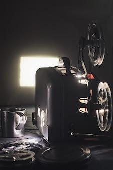 오래된 시네마 프로젝터와 어둠 속에서 빛나는 스크린