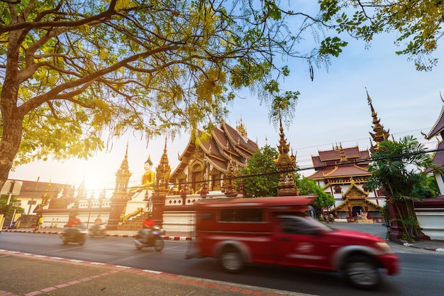Old city moat to busy street with many red taxi and temple of the evening in chiang mai
