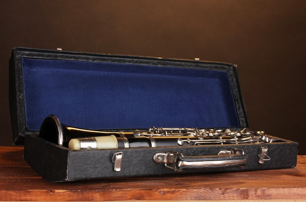 Old clarinet in case on wooden table on brown