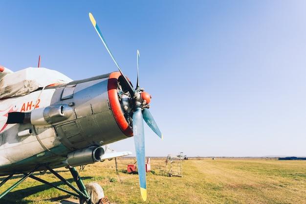 Старый классический самолет антонов (ан-2) кукурузоуборочный комбайн на поле
