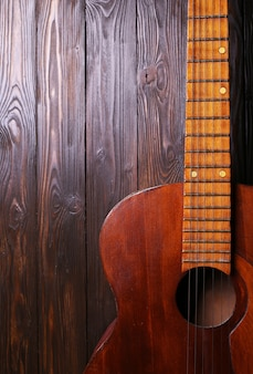 Old classic guitar on wooden surface