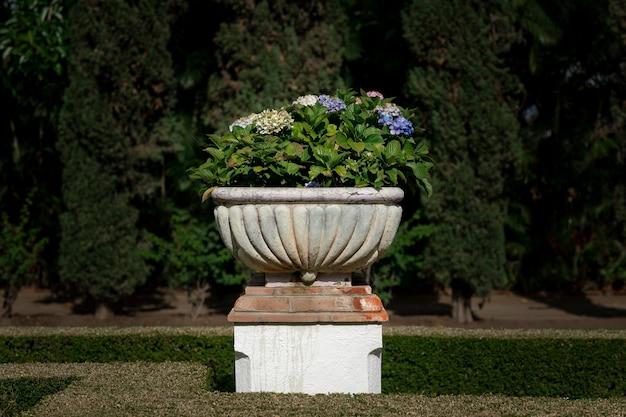 背景にアジサイの花と木と古い古典的な鍋