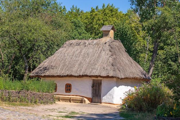 우크라이나에서 초가 지붕이 있는 오래된 점토 집. 밀짚 지붕이 있는 고대 우크라이나 전통 가옥