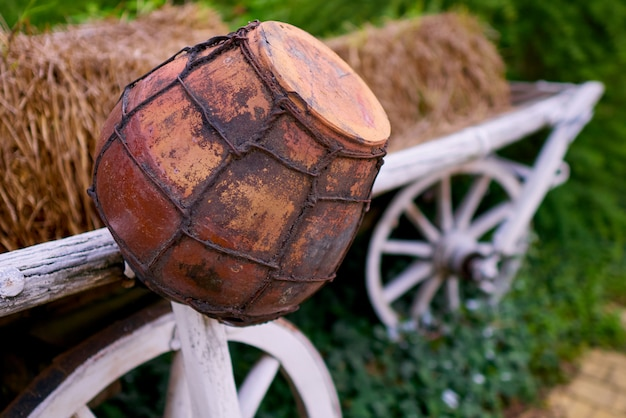 Old clay pot on a cart with hay.